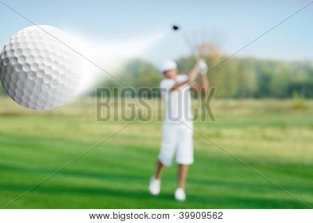 golfer hitting a flying golf ball