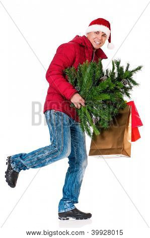 Full length portrait of a young man in winter clothing and Santa hat with shopping bags and artificial fir tree isolated on white background