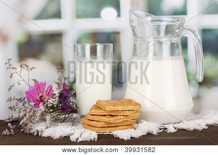 Pitcher and glass of milk with cookies on wooden table on window background