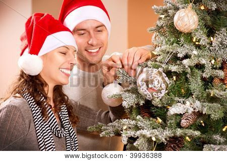 Happy Couple Decorating Christmas Tree in their Home. Smiling Man and Woman together Celebrating Christmas or New Year. Christmas Tree Decoration.Family