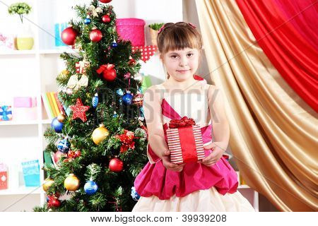 Beautiful little girl in holiday dress with gift in their hands in festively decorated room