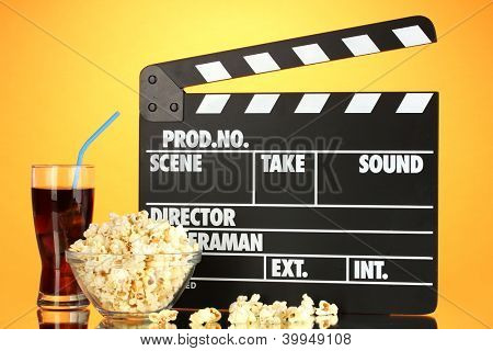 Movie clapperboard, cola and popcorn on orange background