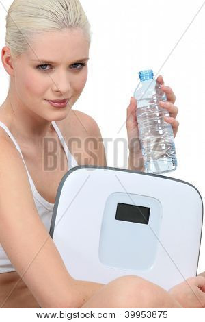 Young woman with a bottle of water and a pair of scales