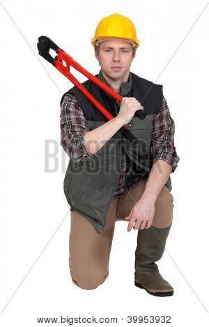 Man kneeling with bolt-cutter