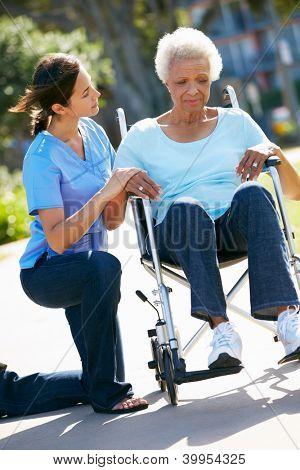 Carer Pushing Unhappy Senior Woman In Wheelchair
