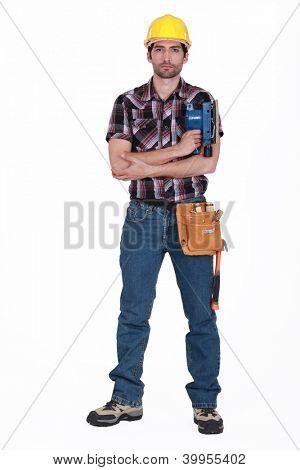 Portrait of a tradesman holding a sander