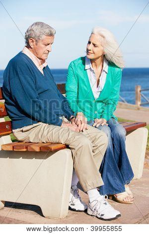 Senior Woman Comforting Depressed Husband Sitting On Bench