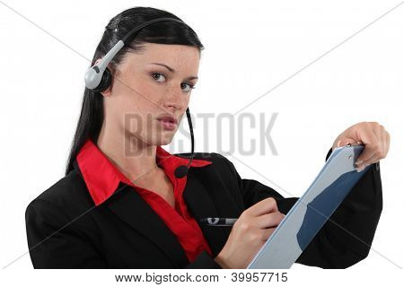 Woman with headphones and microphone writing
