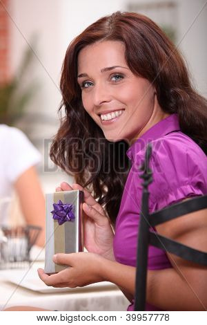 woman in restaurant with fiance smiling at camera with present