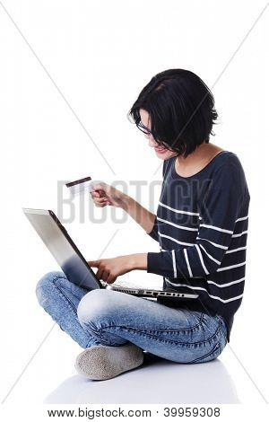Woman with a laptop and a credit card, sitting on the floor, isolated on white. Buying from internet shop