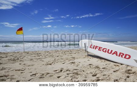 Lifeguard Surfboard And Safe Flag At Beach