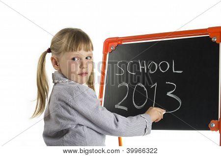 Little girl teaching near board in studio
