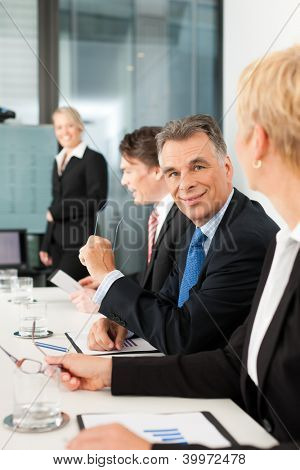 Business - presentation within a team, a female, colleague is standing on the screen