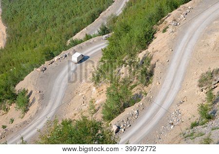 a white van is traveling downhill on the winding dirt road into the Valley of the Kelmend between the albanian mountains