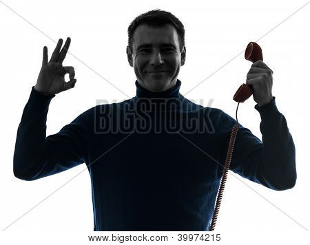 one causasian man on the phone ok sign portrait in silhouette studio isolated on white background