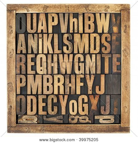 random letters of alphabet - vintage letterpress wood type blocks in rustic box isolated on white