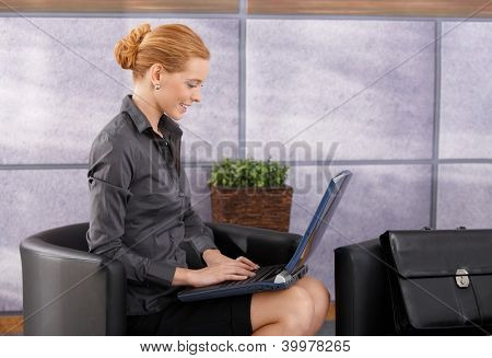 Portrait of smiling businesswoman working on laptop computer in office lobby, side view.