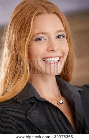 Closeup portrait of happy laughing young businesswoman smiling at camera.