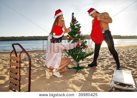Sexy Santa's helpers decking the Christmas tree and Santa looking into the sack at the tropical beach