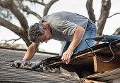 stock photo of shingle  - Close up view of man using crowbar and saw to remove rotten wood from leaky roof decking - JPG