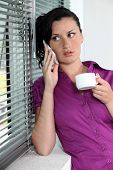 Woman with telephone and coffee cup