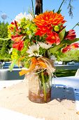 image of centerpiece  - White orange and green wedding flower arrangements with burlap as the centerpieces for table settings at an outdoor reception - JPG
