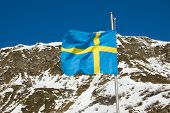 pic of sweden flag  - A Swedish Flag is waving in the mountain wind - JPG