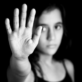 stock photo of gender  - Black and white image of a girl with her hand extended signaling to stop useful to campaign against violence - JPG