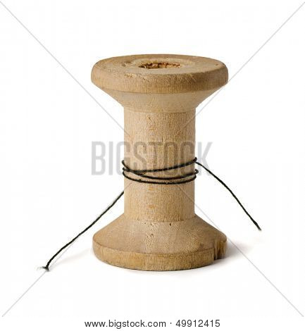 Old wooden spool with leftover threads isolated on white