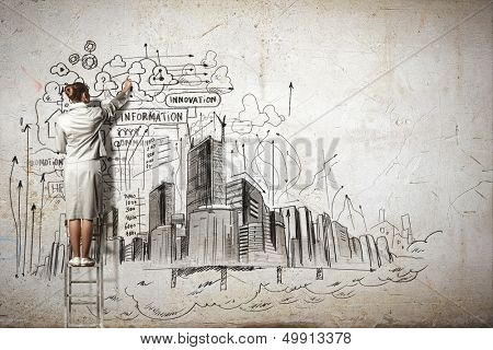 Businesswoman standing on ladder and drawing sketch on wall