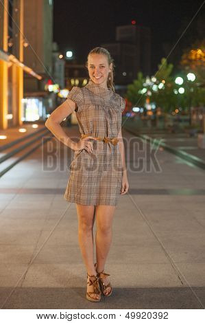 Beautifull girl stay at the square in the night.