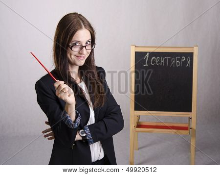 Portrait of the teacher, with a pointer and a Board in the background