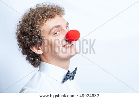 Young studen or Businessman with a red clown nose. Studio shot. Head and shoulders.