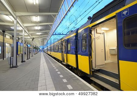 "VENLO, NETHERLANDS - JUNE 22: Commuter train on a train station of Venlo, Netherlands on June 22, 2013. Dutch trains are on the whole punctual with 94% (2012) of train services labeled ""on time"""