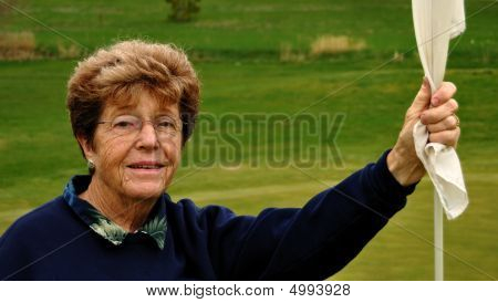 Portrait Of Senior Woman Golfer Holding A Flagstick