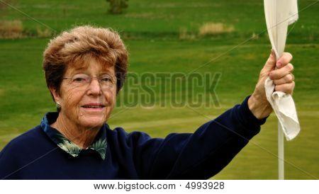 Portrait Of Senior Woman Golfer Holding A Flagstick
