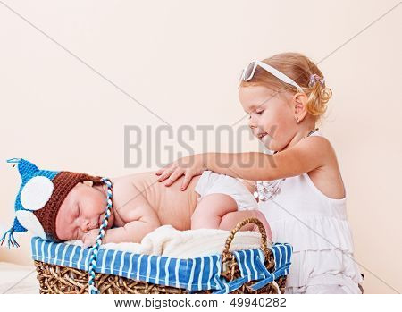 Cute baby sleeping in a basket and a toddler girl