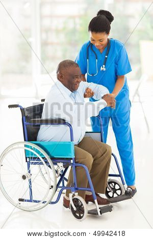 friendly african caregiver helping senior man getting up from wheelchair