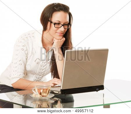 A business woman is drinking tea at the desk - on white background