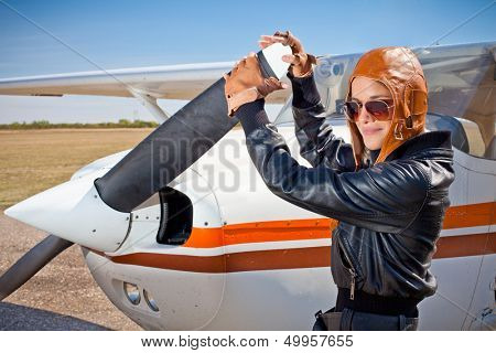 Portrait of female pilot  with plane propeller.