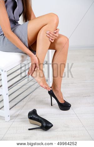 Girl with sore foot isolated on white