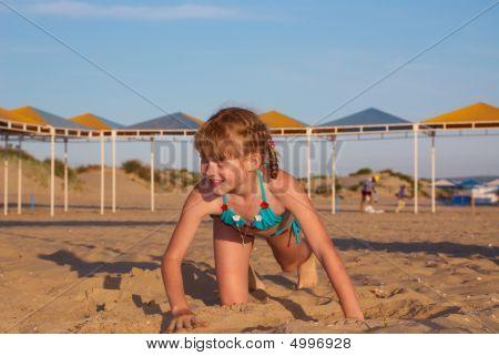 The Girl Creeps On Beach Sand