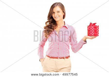 Attractive smiling woman holding a gift box and posing isolated on white background