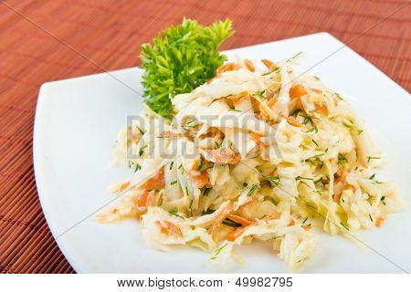 Low fat vegetable salad coleslaw (cabbage, carrot, dill,  mayonnaise) on plate at restaurant table