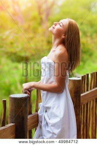 Bonita mujer envuelta en pie de hoja en blanco en balcón en lujoso hotel spa, disfrutando de pacífica natur