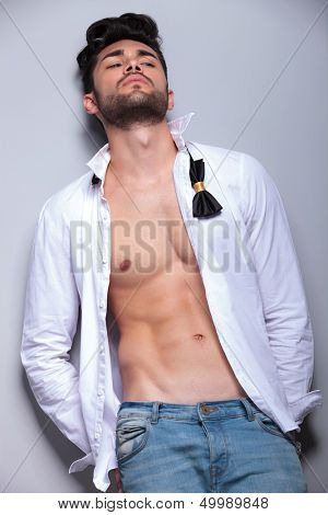 sexy casual young man leaning back and looking away from the camera while holding his hands in his back pockets. on gray background
