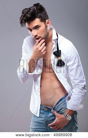 sexy casual young man touching his lower lip with his thumb while looking at the camera. on gray background
