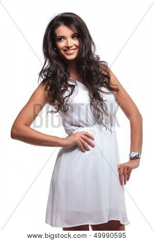 young beautiful woman looking away and smiling while holding her hand on her hip. isolated on a white background