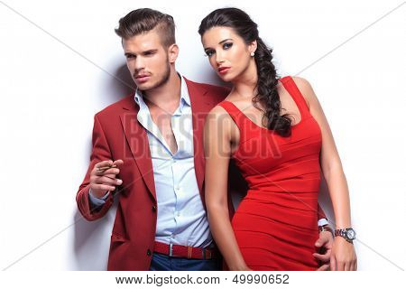 fashion man and woman, man smoking and looking away and woman looking at the camera. casual couple leaning against a white wall