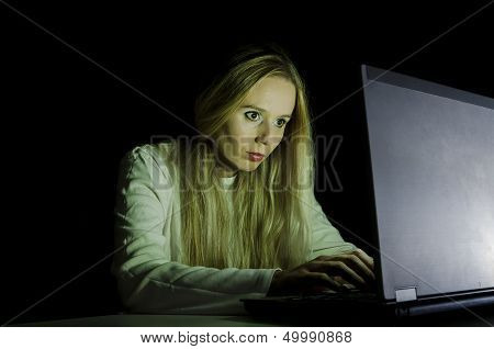 blonde woman working on a computer by night